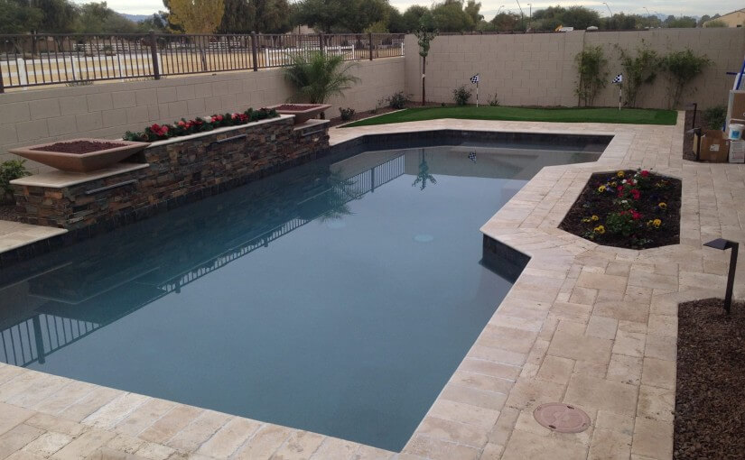 Beautiful pool with elevated flower bed placed between fire features by New Image's Gilbert Pool Service