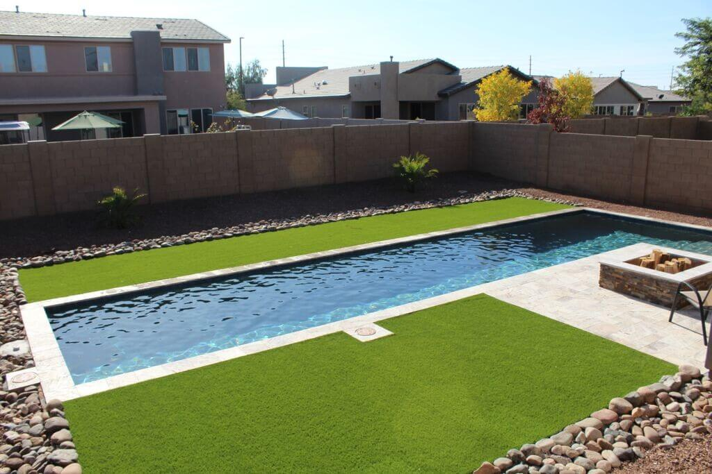 Long rectangular pool sided with synthetic fields and fire pit by New Image, Mesa's landscaping company