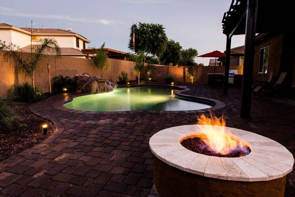 Lit pool with overhanging rock waterfall and pool-side lighting by New Image, Mesa's landscaping company