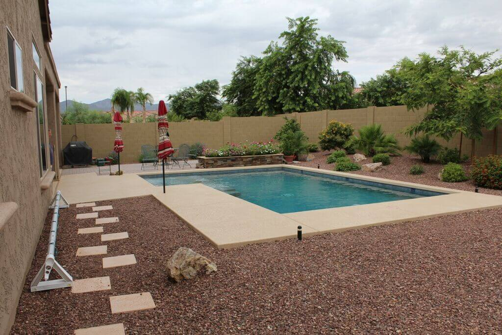 Pool with overlooking flower bed surrounded by rocks and flora by New Image, Mesa's landscaping company