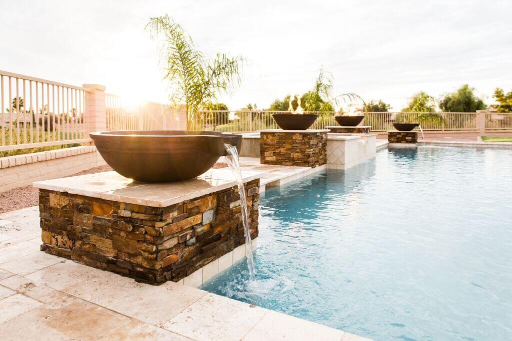 Multicolored textured stone pillars holding fire and water features by New Image, Mesa's landscaping company