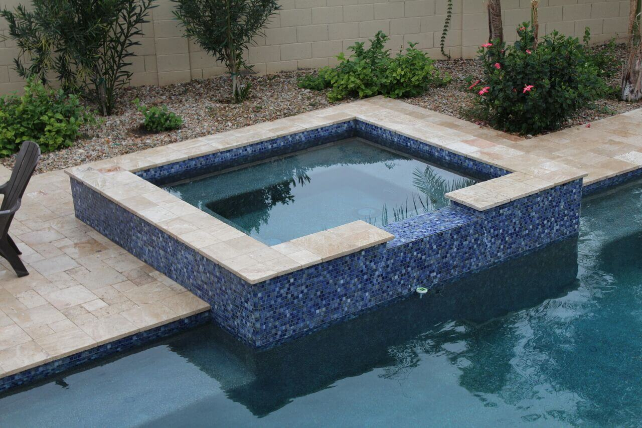 Bright blue mosaic-patterned hot tub overlooking pool by New Image's Mesa & Scottsdale pool service
