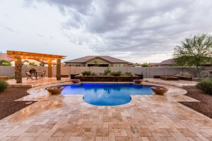 Stunning lit pool overlooked by elevated stone- textured plant bed by New Image's Mesa & Scottsdale pool service