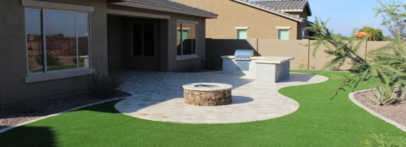 Beautiful paved pattern surrounded by synthetic turf by New Image, Mesa's landscaping company