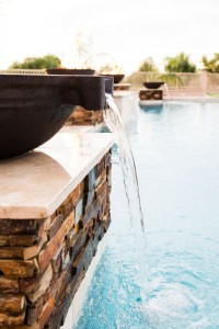 Close-up of textured pillar with mounted water feature overlooking pool by New Image, Mesa & Scottsdale landscaping company