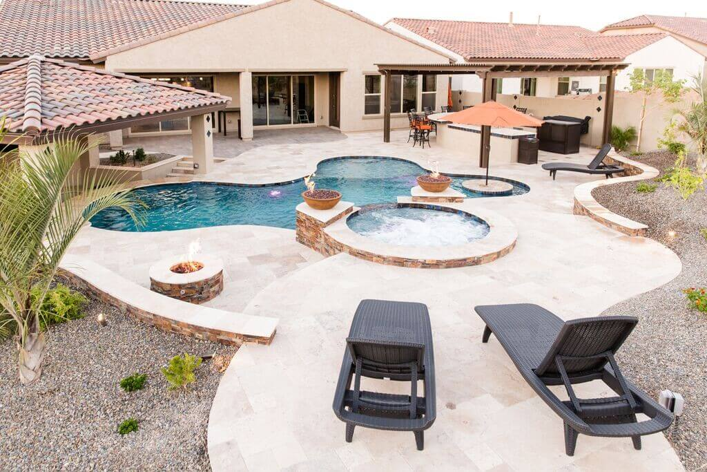 Luxurious pool and spa with sun-bathing platform and umbrella by New Image, finest of Mesa's landscaping companies
