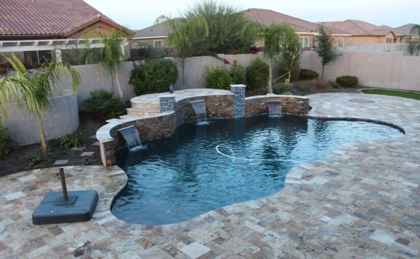 Custom-shaped pool with elevated platform structure with three built-in waterfalls by New Image's Mesa & Scottsdale pool service