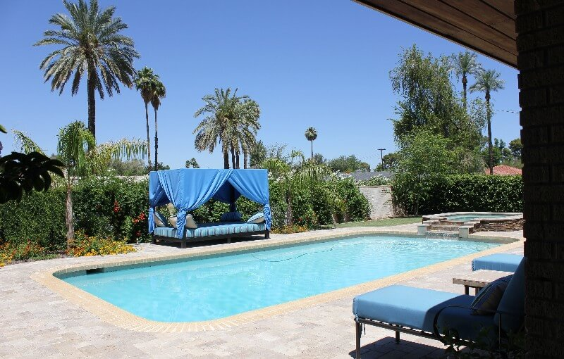 Simple luxurious pool and spa with flora and blue canopy bed by New Image's Mesa & Scottsdale pool service