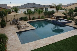 L-shaped pool, spa, and fire pit outlined with beautiful flora by New Image's Mesa & Scottsdale pool service